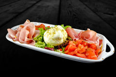 Appetizer plate with prosciutto crudo, chopped tomatoes, salad and burrata. stock photo