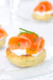 Appetizer - potato bun with salted salmon and caviar. Appetizer - potato bun with salted salmon, red caviar and green onion on a glass plate closeup vertical Royalty Free Stock Photo