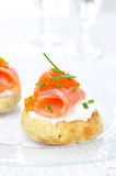 Appetizer - potato bun with salted salmon, red caviar and chives. On a glass plate close-up vertical Royalty Free Stock Photography