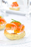 Appetizer - potato bun with salted salmon, red caviar. And green onion on a glass plate closeup Stock Photos