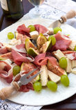 Appetizer with prosciutto, figs, cheese and grapes Stock Image