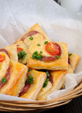 Appetizer of puff pastry with salami. Cheese and cherry tomatoes Stock Photo