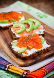 Appetizer with red caviar, avocado, salmon and creamcheese Stock Image