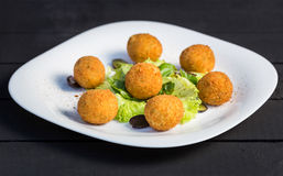 Appetizer rice balls cooked in deep fat served with greens. Appetizer arancini, rice balls stuffed with meat cooked in deep fat served with greens on white plate Royalty Free Stock Photos