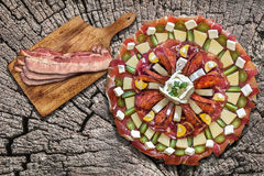 Appetizer Savory Dish Meze with Bacon Rashers on Old Cracked Stump as Improvised Picnic Table Stock Photo