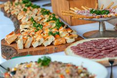 Appetizer of savory pizzas and other salami in a wedding party Stock Image