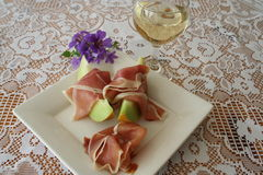Appetizer with Serrano ham. Serrano ham and Galia melon together with a glass of white wine Royalty Free Stock Photo