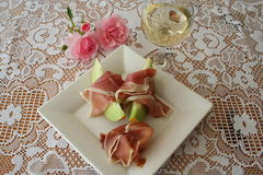 Appetizer with Serrano ham. Serrano ham and Galia melon together with a glass of white wine Stock Images