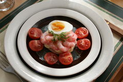 Appetizer with shrimps. Egg and tomatoes on plate at laid table Stock Images
