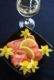 Appetizer with smoked salmon. And lemon, a glass of white wine and decoration with mini Daffodils Stock Photos