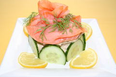 Appetizer with smoked salmon. Small sandwich gateau with salmon,cucumber,lemon and dill Stock Image