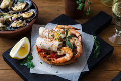 Appetizer with spicy tomato squids and shrimps on toast Royalty Free Stock Photography