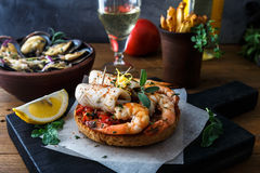 Appetizer with spicy tomato squids and shrimps on toast Royalty Free Stock Images