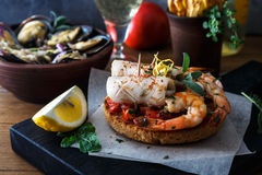 Appetizer with spicy tomato squids and shrimps on toast Stock Photos