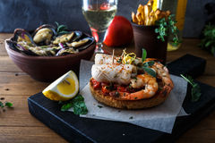 Appetizer with spicy tomato squids and shrimps on toast Stock Photo