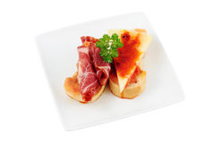 Appetizer of spine and cheese. Snack plate of cheese and tomato paprika pork with parsley and olive oil on toasted bread cut off and isolated Royalty Free Stock Photography