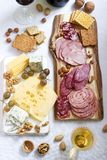 Appetizer of various types of sausages, meats, cheeses and crackers on a wooden board, served to wine royalty free stock image