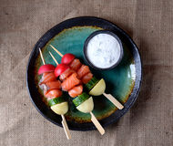 Appetizer on wooden skewers from lightly salted salmon, boiled potatoes, cucumber and radish. Stock Image
