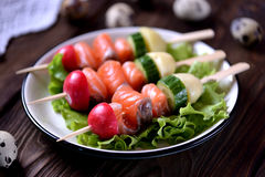 Appetizer on wooden skewers from lightly salted salmon, boiled potatoes, cucumber and radish. Royalty Free Stock Photos