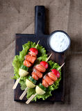 Appetizer on wooden skewers from lightly salted salmon, boiled potatoes, cucumber and radish. Stock Photos
