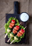 Appetizer on wooden skewers from lightly salted salmon, boiled potatoes, cucumber and radish. Stock Images