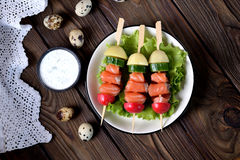 Appetizer on wooden skewers from lightly salted salmon, boiled potatoes, cucumber and radish. Stock Photography
