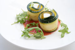 Appetizer of zucchini  with cheese and arugula in a plate. Appetizer of zucchini and arugula in a white plate with tomato sauce Stock Photography