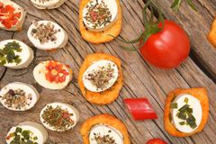 Appetizers cheese and bruschetta with herbs, tomato and chilli peppers Royalty Free Stock Photography