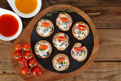 Appetizers with cheese spread and tomato on wooden background. Horizontal shot Stock Photo