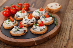 Appetizers with cheese spread and tomato on wooden background Stock Photos