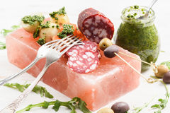 Appetizers on pink salt block. Salami, potatoes, arugula, green. And calamata olives with green chimichurri sauce and vintage forks on white background closrup Stock Photo