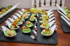 Appetizers in Porcelain spoons on black stone platter royalty free stock photo