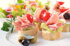 Appetizers with salami. Baguette slices with delicious Italian salami and cherry tomatoes stock image