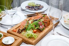 Appetizers of seafood and meat on wooden plate Royalty Free Stock Images