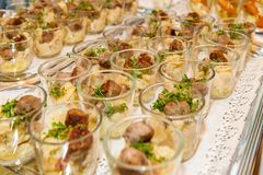 Appetizers in small glasses in rows stock photo