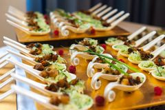 Appetizers in spoons on golden platter stock photography