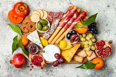 Appetizers table with antipasti snacks. Cheese and meat variety board over grey concrete background. Top view, flat lay. royalty free stock image