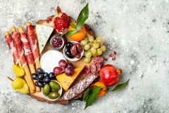 Appetizers table with antipasti snacks. Cheese and meat variety board over grey concrete background. Top view, flat lay. Appetizers table with antipasti snacks Stock Image