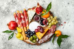 Appetizers table with antipasti snacks. Cheese and meat variety board over grey concrete background. Top view, flat lay. stock photography