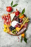 Appetizers table with antipasti snacks. Cheese and meat variety board over grey concrete background. Top view, flat lay. Stock Photos