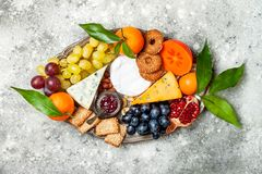 Appetizers table with antipasti snacks. Cheese variety board over grey concrete background. Top view, flat lay. Royalty Free Stock Images