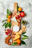 Appetizers table with antipasti snacks. Cheese variety board over grey concrete background. Top view, flat lay. royalty free stock photography
