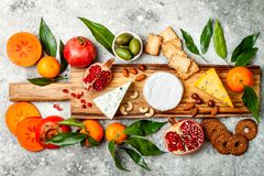 Appetizers table with antipasti snacks. Cheese variety board over grey concrete background. Top view, flat lay. Appetizers table with antipasti snacks. Cheese Stock Photos