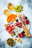 Appetizers table with antipasti snacks and wine in glasses. Authentic traditional spanish tapas set, cheese and meat platter. Over grey concrete background. Top stock photography