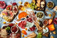Appetizers table with antipasti snacks and wine in glasses. Bruschetta or authentic traditional spanish tapas set, cheese and meat. Platter over grey concrete royalty free stock image