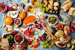 Appetizers table with antipasti snacks and wine in glasses. Bruschetta or authentic traditional spanish tapas set. Cheese and meat platter over grey concrete stock image