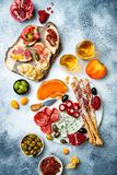Appetizers table with antipasti snacks and wine in glasses. Bruschetta or authentic traditional spanish tapas set. Cheese and meat platter over grey concrete stock photos