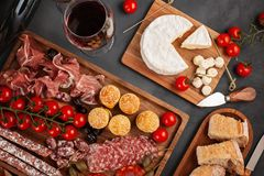 Appetizers table with differents antipasti, cheese, charcuterie, snacks and wine. Mini burgers, sausage, ham, tapas, olives, chees. E variety board and baguette stock image