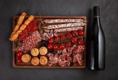 Appetizers table with differents antipasti, cheese, charcuterie, snacks and wine. Mini burgers, sausage, ham, tapas, olives, chees. E variety board and baguette royalty free stock photography