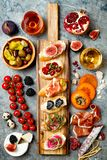 Appetizers table with italian antipasti snacks and wine in glasses. Brushetta or authentic traditional spanish tapas set. Cheese variety board over grey stock images